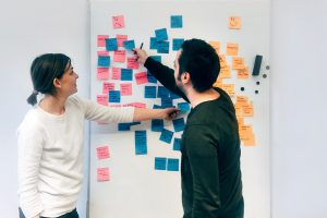 Two people collaborating on a whiteboard with sticky notes